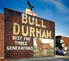 """Painted sign saying """"Bull Durham, Best for three generations"""" and a picture of a bull on the side of a brick building."""